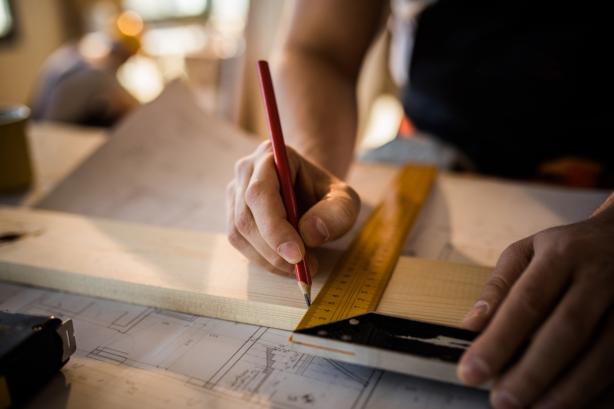Close up of unrecognizable carpenter making measurements and drawing on a plank.